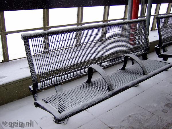 Bankje op een treinstation met sneeuw. Het bankje heeft twee leuningen in het midden om te voorkomen dat er mensen op gaan liggen.